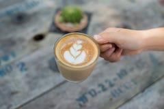 Mains femelles tenant une tasse de café au-dessus de table en bois, vue supérieure Image stock