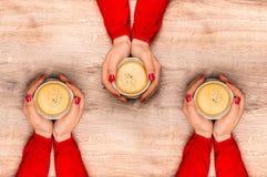 Mains femelles tenant une tasse de café chaud Image stock