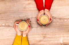Mains femelles tenant une tasse de café chaud Photographie stock
