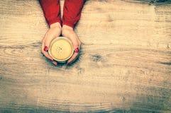 Mains femelles tenant une tasse de café chaud - rétro style Photos stock