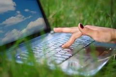Mains travaillant sur l'ordinateur portable Photo stock