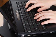 Mains travaillant sur l'ordinateur portable Photographie stock libre de droits
