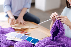 Mains femelles tricotant un chapeau pourpre Images libres de droits