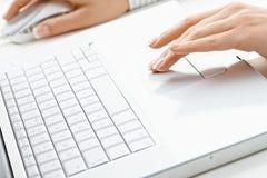 Mains femelles utilisant l'ordinateur portatif Image stock