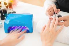Mains femelles utilisant le dessiccateur portatif de lumière UV photographie stock