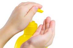 Mains femelles utilisant le savon liquide sur le blanc images stock