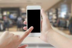 Mains femelles utilisant le téléphone portable sur le supermarché brouillé de fond Images libres de droits