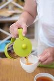 Mains femelles versant le thé dans un  de Ñ  photo stock