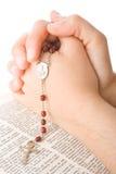 Mains fermées dans la prière avec un rosaire Image libre de droits