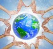 Mains formant un cercle avec la terre de planète Image libre de droits
