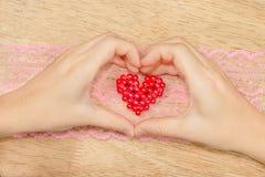 Mains formant un coeur montrant un en forme de coeur du rouge Photographie stock libre de droits