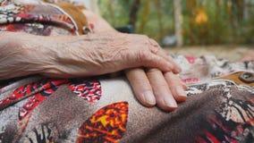 Mains froissées de femme supérieure Bras de vieux se reposer de grand-mère extérieur Fermez-vous vers le haut du mouvement lent d banque de vidéos