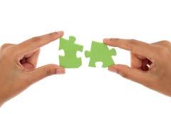 Mains fusionnant deux morceaux de puzzle denteux contre le blanc Photographie stock
