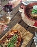 Mains grillant des verres de vin dans un restaurant italien Image libre de droits
