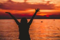 Mains heureuses d'ouverture de femme au coucher du soleil Image libre de droits