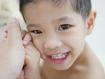 Mains heureuses du ` s de bébé et son visage de sourire dans sa main du ` s de père photo libre de droits