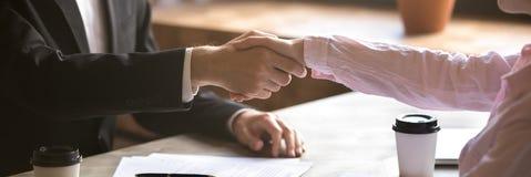 Mains horizontales de plan rapproché de photo de l'homme d'affaires et de la femme d'affaires se serrant la main photo libre de droits