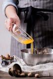Mains humaines ajoutant le jaune de la glace pour faire des biscuits Image stock