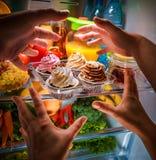 Mains humaines atteignant pour le gâteau doux la nuit dans le refrige ouvert Image libre de droits