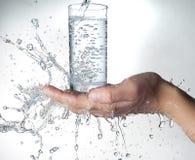 Mains humaines avec de l'eau éclaboussant sur eux Photos libres de droits