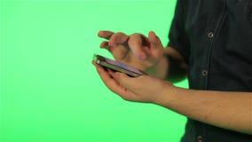 Mains humaines avec le téléphone sur l'écran vert banque de vidéos