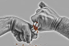 Mains humaines cassant violemment des cigarettes Image libre de droits