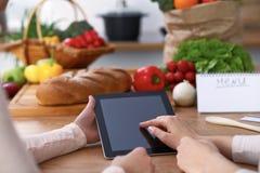 Mains humaines de deux personnes féminines employant le touchpad pour faire le menu dans la cuisine Le plan rapproché de deux fem Image libre de droits
