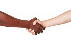 Mains humaines noires et blanches dans une poignée de main moderne Photo stock