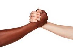 Mains humaines noires et blanches dans une poignée de main moderne Image libre de droits
