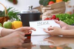 Mains humaines se dirigeant dans le carnet avec le secteur d'espace de copie Femme deux faisant le menu dans la cuisine, plan rap Photos stock