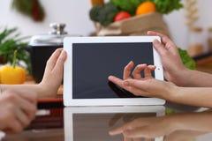 Mains humaines se dirigeant dans le pavé tactile avec le secteur d'espace de copie Femme deux faisant le menu dans la cuisine, pl Photographie stock