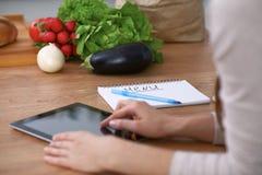 Mains humaines utilisant le pavé tactile dans la cuisine Plan rapproché de femme faisant des achats en ligne en la tablette et la Images stock