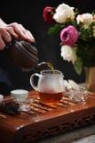 Mains humaines versant le thé de la théière d'argile dans la cruche en verre Images libres de droits