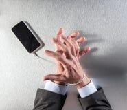 Mains impatientes d'homme d'affaires hantées avec la dépendance mobile d'esclavage et de technologie photographie stock