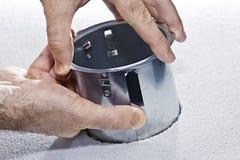 Mains installant l'appareil d'éclairage de bac en métal images libres de droits