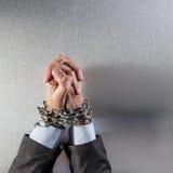 Mains jointives d'homme d'affaires attachées avec la chaîne priant pour le crime d'entreprise photographie stock libre de droits