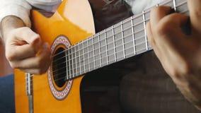 Mains jouant sur la guitare acoustique dans le mouvement lent banque de vidéos