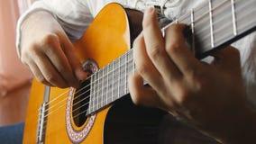 Mains jouant sur la guitare acoustique dans le mouvement lent clips vidéos