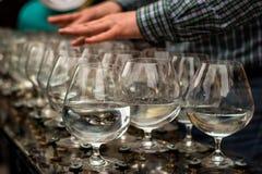 Mains jouant sur les verres avec de l'eau Photo libre de droits