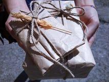 Mains jugeant des cadeaux enveloppés en papier brun de vieux vintage et attachés avec la corde Image libre de droits