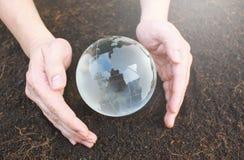 Mains jugeant la terre faite à partir du verre Photographie stock