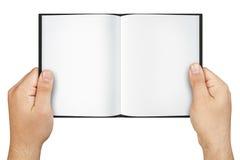 Mains jugeant le livre ouvert de blanc d'isolement photographie stock libre de droits