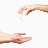 Mains laissant tomber le cube blanc sur le fond blanc Photographie stock libre de droits