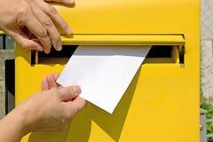 Mains laissant tomber une lettre dans une boîte de lettre Image libre de droits