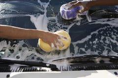 Mains lavant la voiture avec des éponges photo libre de droits