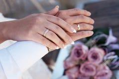 Mains mâles et femelles avec des boucles de mariage Photographie stock libre de droits