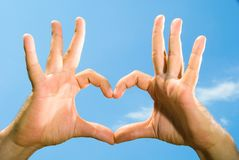 Mains mâles pliées sous forme de coeur Photographie stock
