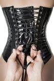 Mains mâles serrant vers le haut un corset image stock