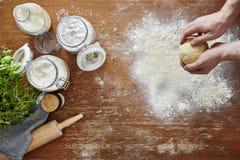 Mains malaxant des utilités de farine et de cuisine de la pâte de pâtes sur l'espace de travail en bois Image libre de droits