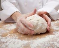 Mains malaxant la pâte de pain Photo libre de droits